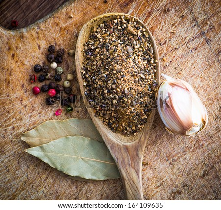 spices in a wooden spoon with laurel leaves on a cutting board
