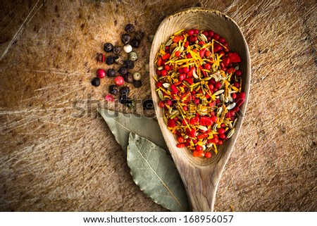 spices in a wooden spoon with laurel leaves on cutting board