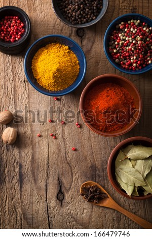 spices in bowls: pink and black pepper, paprika powder, curry, bay leaf