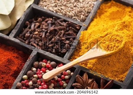 spices in box: pink black pepper, paprika powder, curry, bay leaf; anise; clove; cumin