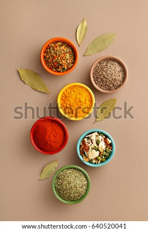 Spices in colorful bowls viewed from above. Various seasonings on a dark background. Italian mix, cumin, chili pepper, curry powder, Himalayan salt, pepper, garlic, cinnamon, dried tomato. Top view #640520041