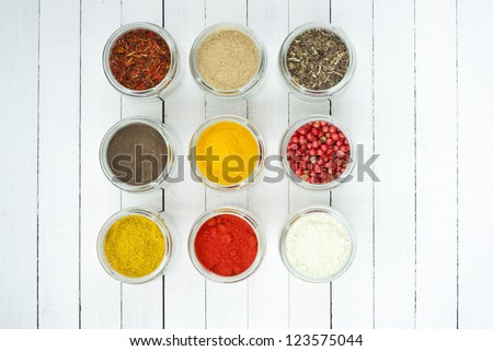 spices in glass jars on white wooden table, top view
