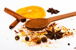 Spices kit concept. Spoon with spices, dried orange, cinnamon stick, cardamom and nutmeg on white background. Spices kit for preparing mulled wine or hot beverage, close up. Mulled wine spices kit.