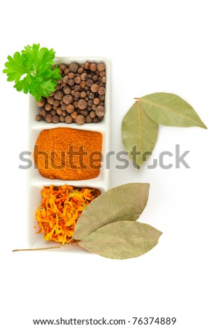 Spices. Mix of different herbs: pepper balls, saffron, chili, laurel, and fresh parsley on white background