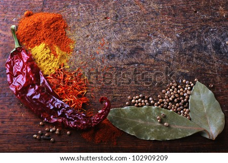 Spices on a old wooden cutting board with saffron, curry and chili pepper