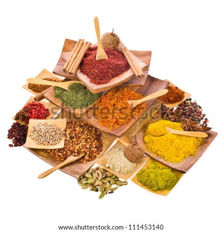 spices powders and solid different colored ground with wooden spoons in a wooden coasters set in a pyramid isolated on white background