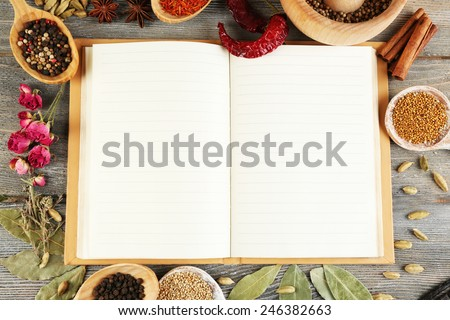 Spices with recipe book on rustic wooden table background