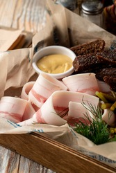 Spicy and salty pork fat with rye croutons and spicy mustard, close up, appetizing photo of a traditional ukrainian snack