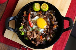 Spicy and sizzling pork sisig is a favorite for Filipinos and goes well wit ice cold beer.