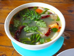 spicy asian retail catfish soup with vegetables (Tom Yum) on wooden table