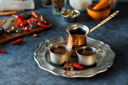 Spicy Aztec or Mexican Hot Chocolate in Two Cups on a Metal Tray with Peppers, Spices, and Other Ingredients in Background