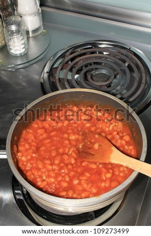 Spicy BBQ beans in saucepan with wooden spoon cooking on electric stove.