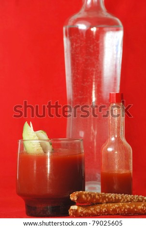 Spicy Bloody Mary ingredients with vodka, tomato juice and spicy hot sauce against bright red background.