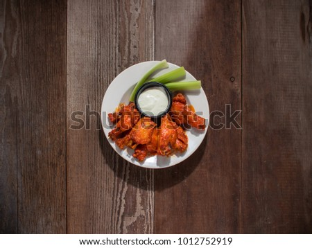 Spicy Buffalo Wings on plate with Blue cheese and celery sticks. #1012752919