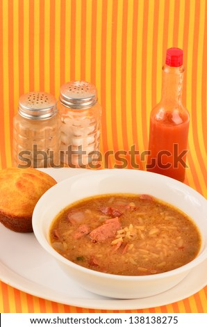 Spicy Cajun Cooking - Sausage Gumbo in white bowl on white plate with cornbread muffin against colorful orange and yellow background.  Salt and Pepper Shaker and bottle of Louisiana Hot Sauce.