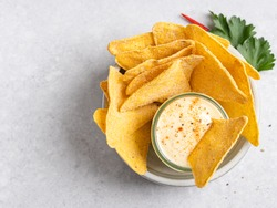 Spicy cheese sauce (dip) with nachos (tortilla chips) ready to eat. Mexican snack or appetizer. Traditional fast food. Top view, concrete background. Copy space.