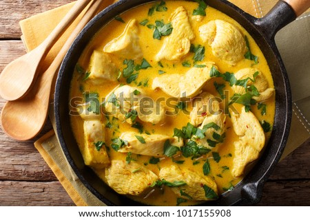Spicy chicken in a sauce of coconut milk close-up in a frying pan. horizontal top view from above