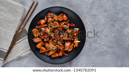 spicy chicken in sweet and sour sauce with chili pepper. teriyaki chicken's  with  sesame seeds. Chinese cuisine, Thai cuisine. Japanese food, copy space, recipe background, food flat lay