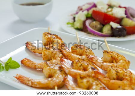 Spicy chili prawn skewers with a traditional Greek salad and dressing