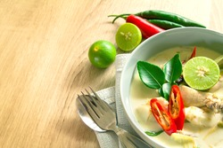 Spicy creamy coconut soup with chicken , Thai food called Tom Kha Gai on wooden table