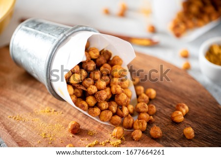 Spicy crispy roasted chickpeas with paprika, curry and hot chili pepper, selective focus. Tasty vegetarian and vegan chickpea snack. Stockfoto ©