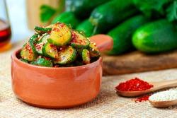 Spicy cucumber snack in Korean - Korean cucumber salad, in a brown ceramic bowl, on a blue background, on a beige Mat. In the background, cucumbers, sesame oil.