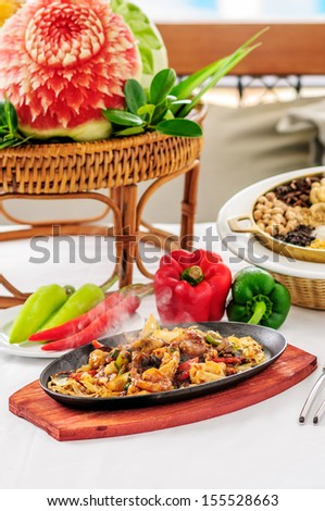 Spicy fried seafood on a hot pan. Smoke to taste. And beautifully decorated. - stock photo
