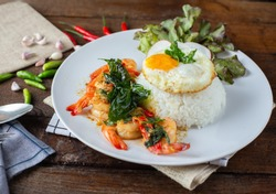 Spicy fried shrimp with basil and chili, serve with rice and egg in white ceramic plate on wood table, Thai style food. Food issue.