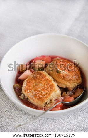 Spicy fruit cobbler in a white bowl, selective focus