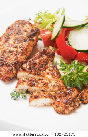 Spicy grilled chicken white meat with salad and herbs