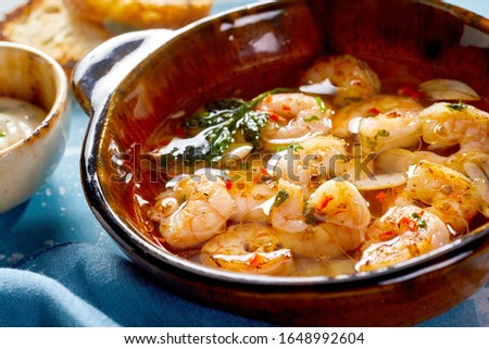 Spicy grilled fresh scampi or lobster with garlic and herbs served in a brown ceramic bowl in close up Foto d'archivio ©