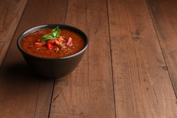Spicy Homemade Gazpacho Soup with basil on wood table. Summer tomatoes cold soup in bowl with place for text. Copy space.