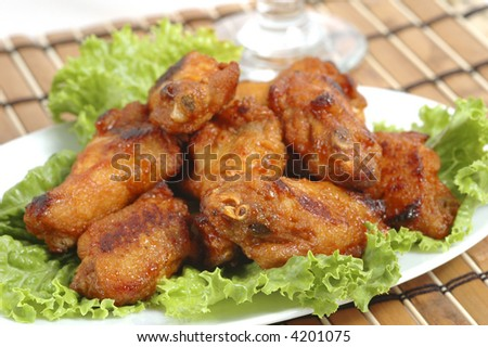 Spicy hot barbecued wings on bed of lettuce. - stock photo