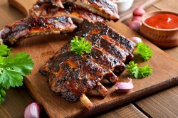 Spicy hot grilled spare ribs on cutting board, close up view