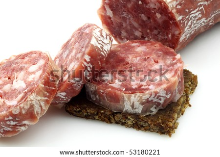 spicy Italian salami sausage and slices on rye bread on a white background