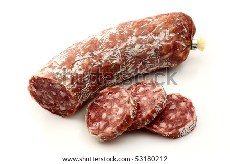 spicy Italian salami sausage and some slices on a white background