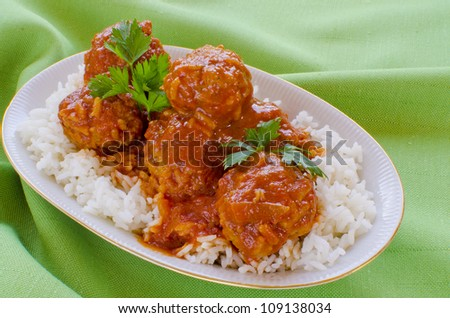 Spicy meatballs with rice in tomato sauce