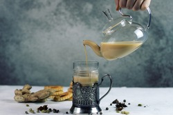 Spicy milk Indian tea Masala poured into a glass from a teapot. Aromatic hot drink with cloves and spice