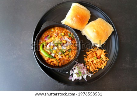 Spicy Misal Pav or usal Pav is a traditional snack or Chaat food from Maharashtra, India. Served with chopped onion, lemon wedges and farsan. Selective focus with copy space Stockfoto ©