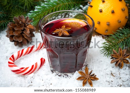 spicy mulled wine in the glass on the snow and caramel candy, horizontal