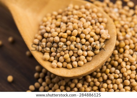 Spicy mustard seeds in a wooden background