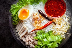 Spicy Noodles and Vegetable , Meat , Eggs , Flour with chilli sauce or Schezwan .Rice Noodles in chopsticks .