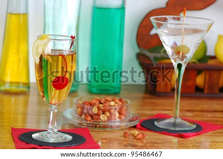 Spicy peanuts and mixed drinks on wooden bar at Happy Hour in Local Pub with colorful bottles in background.