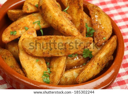 Spicy potato wedges in terracotta dish.