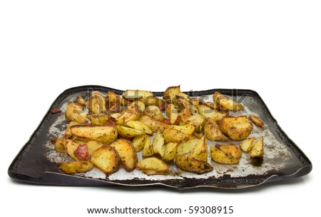 Spicy Potato Wedges with Chorizo Sausage on baking tray straight from oven. - stock photo