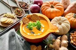 Spicy pumpkin soup seasoned with ginger and garlic, served in a hollowed pumpkin with croutons, parsley and pumpkin seeds. Autumn food background, text space.