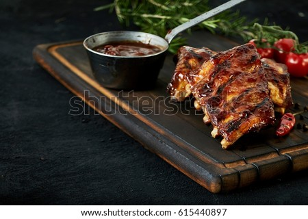 Spicy rack of spare ribs with marinade in a small saucepan and a red hot chili pepper served on an old wood chopping board in a restaurant , close up view with copy space Foto stock ©