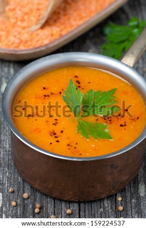Spicy red lentil soup in a copper saucepan, close-up, top view, vertical