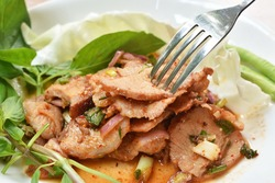 spicy roasted pork Thai salad eat with fresh basil leaf and cabbage on plate stabbing by silver fork