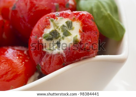 Spicy round red peppers stuffed with cheese, garnished with basil. The white bowl.
